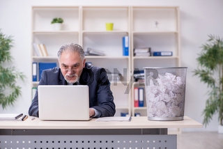 Old businessman rejecting new ideas with lots of papers