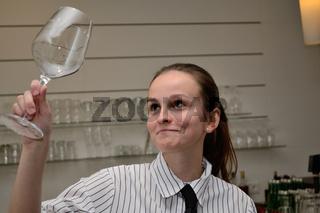 junge Kellnerin prueft Weinglas