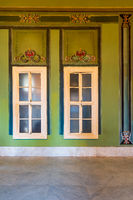 Closed windows and beautiful elegant carved frames on green wall with ornate border and marble floor