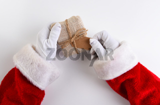 Overhead shot of Santa Claus hands holding a fabric wrapped Christmas Present with a blank gift tag.