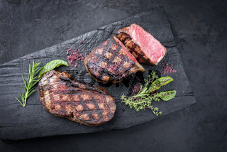 Barbecue dry aged wagyu roast beef steak with lettuce and herbs as top view on a rustic charred wooden board