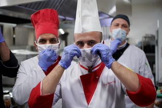 group chefs standing together in the kitchen at restaurant wearing protective medical mask and gloves in coronavirus new normal concept