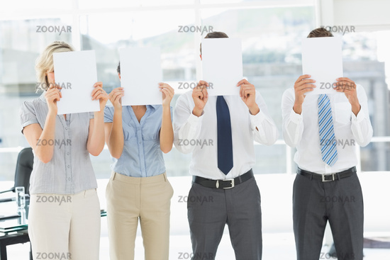 Business people with blank paper in front of faces in office