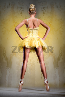 Beautiful ballerina in yellow tutu on point posing over obsolete wall