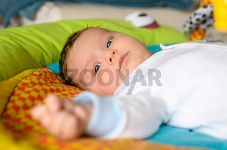 Cute baby boy is lying on colourful carpet