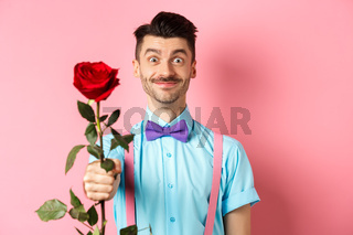 Valentines day and romance concept. Funny guy with moustache giving red rose and smiling, making romantic gesture on date, standing over pink background