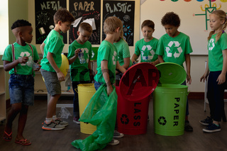 Group of schoolchildren holding color coded recycling bins and bags  in an elementary school classro