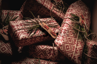 Many christmas presents piled up in a box with creative handmade decorative rustic diy gift wrapped in red retro wrapping paper with natural vintage twine and spruce twigs as decor, hidden away until Xmas Eve