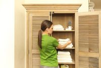 Young woman wearing green t-shirt near cupboard holding towels in laundry room