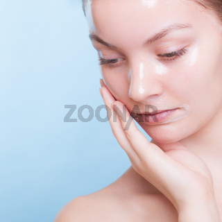 Portrait blond girl in facial mask on blue. Beauty and skin care.