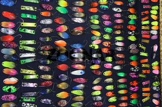 Colorful fishing plugs on black background. Wide assortment of fishing devices
