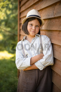 Country girl poses leaning against wooden plank wall of building. Teenage girl in white hat and braces looks at camera crossed arms. Holidays in countryside concept