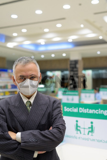 Mature Japanese businessman with mask social distancing at the food court