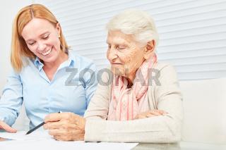 Seniorin bei Finanzberatung liest Vertrag