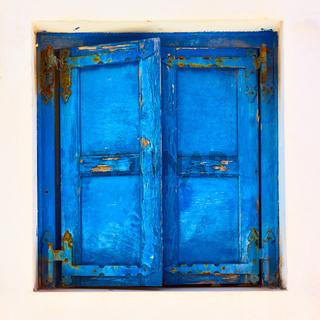 Window with closed blue shutters in Mykonos