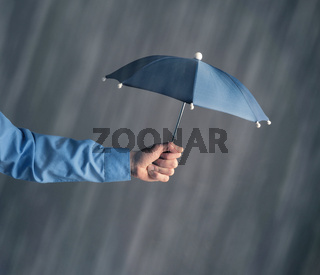 Hand of a businessman with an umbrella in rain