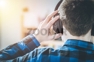 Enjoying music at home: Young Caucasian man is listening to music with headphones, back of the head