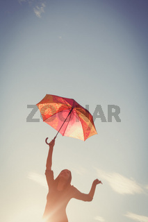 The girl dances with umbrellas in her hands against the clear sky, the picture is tinted in retro colors