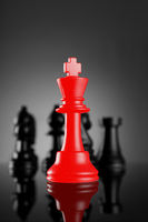 Leadership Red Chess King with pieces on dark background