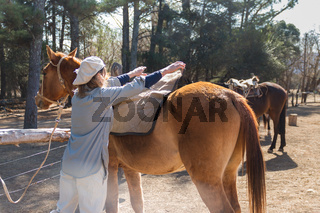 rural woman saddling her horse in the field