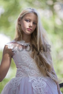Beautiful teenager girl in a white dress on a background of greenery