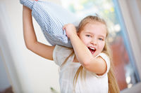 Mädchen mit Kissen macht Kissenschlacht