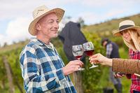 Weinbauer beim Anstoßen mit Glas Rotwein