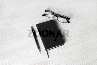 Notebook, glasses and pencil
