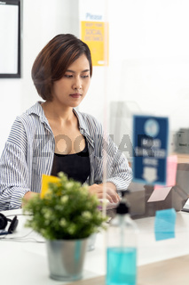Asian businesswoman working in home office with social distancing