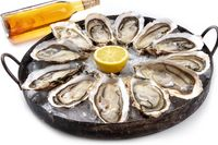A dozen of oysters with wine and lemon on a white background