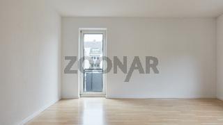 Leerer großer Raum mit Balkontür in Wohnung nach Renovierung