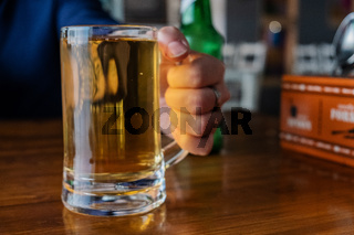 Man's hand holding beer