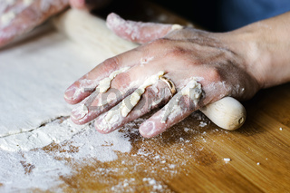 female hands using a rolling pin to pave a dough over a wooden board dirty with flour.