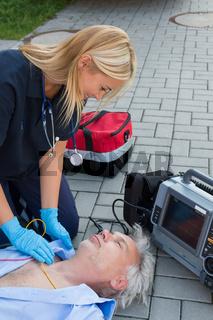 Paramedic examining unconscious elderly man