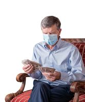 Senior man counting out US dollar bills with face mask and looking worried