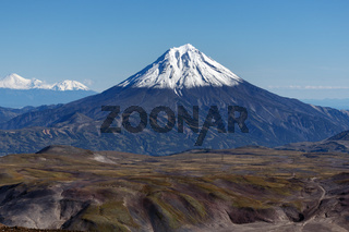 Scenery autumn mountain landscape - view of snow capped cone of volcano