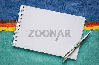 blank art sketchbook against colorful handmade paper