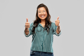 happy asian woman in glasses showing thumbs up