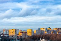 blue clouds over urban houses at spring sunset
