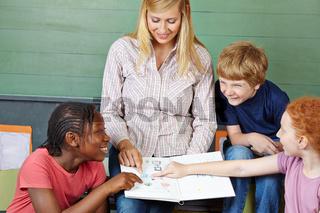 Schüler und Lehrer mit Heft im Unterricht