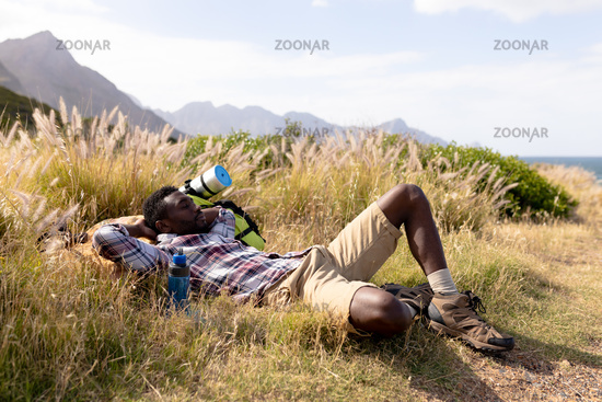 Fit african american man resting and lying in mountain countryside