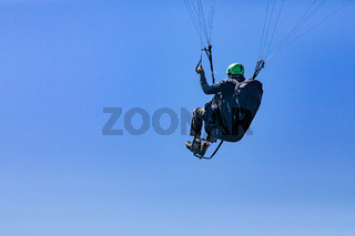 Paraglider flying against the blue sky