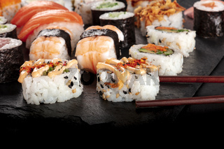 Large sushi set, close-up with chopsticks and copy space on a black background. An assortment of various maki, nigiri and rolls