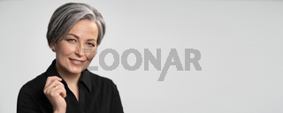 Pretty mature woman smiles with hand near face. Charming gray-haired lady in black blouse on white background. Copy spase for text. Horizontal blank or template for ad banner