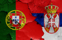 flags of Portugal and Serbia painted on cracked wall