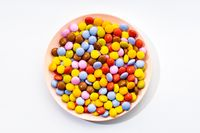 Multicolored Chocolate candy in plate on white background