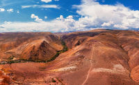 Aerial shot of the textured yellow nad red mountains resembling the surface of Mars
