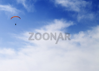 Silhouette of skydiver at sky