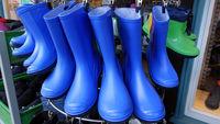 blaue Gummistiefel vor dem Schuhgeschäft