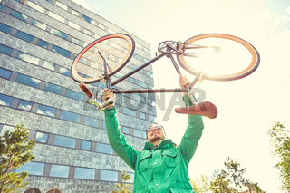 young hipster man rising fixed gear bike in city